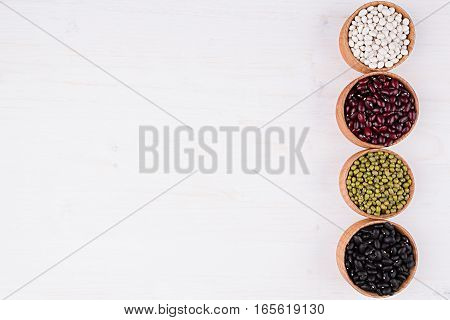 Assortment of kidney beans in a wooden bowls with copy space on white wood background. Top view closeup. Healthy protein food.