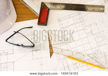 business architecture plans with helmet and drawing tools