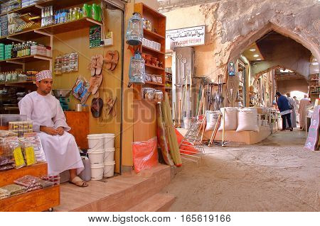 NIZWA, OMAN - FEBRUARY 2, 2012: The Souq in Nizwa Old Town with an Omani man traditionally dressed on the left