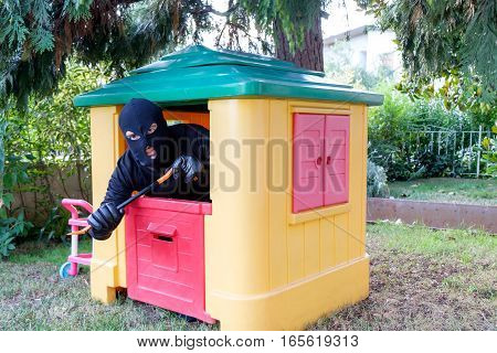 Conceptual Image Of A Thief Forcing A Small Toy House Using A Crowbar