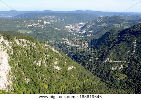 A stunning view of Sainte Claude and the French Jura mountains taken from Belvédère La Roche Blanche outlook point in the summer.