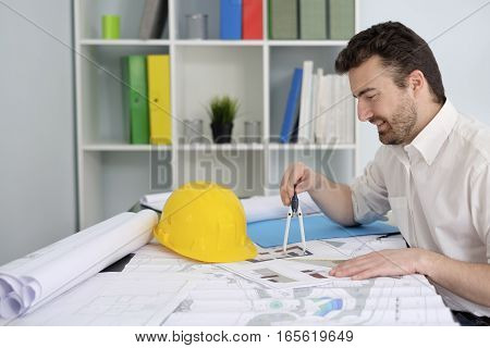Architect Working On His Projects Papers With Compass