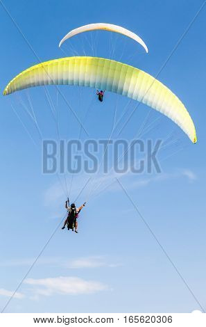 Amateur Paragliders In Blue Sky With Clouds