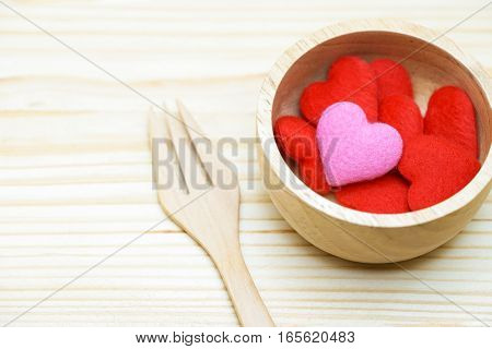 Hearts in wooden bowl with fork love and valentine concept