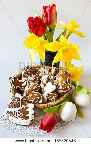 Traditional Czech easter decoration - my own homemade regional gingerbread cakes in the wicker nest with tulip and daffodils flowers on white background. Spring easter holiday arrangement.