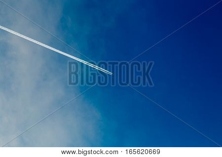 Trace from the plane in a blue sunny sky