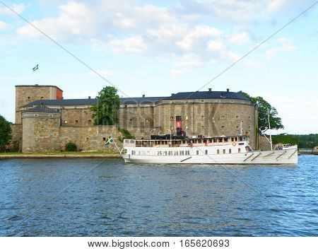White Boat and the Vaxholm Fortress, the historic fortification in Stockholm Archipelago, Sweden