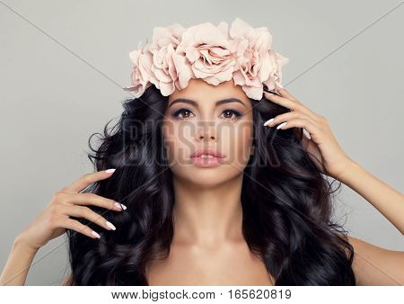 Spa Beauty. Beautiful Woman in Spring Flowers Wreath. Perfect Model with Natural Makeup Healthy Skin Curly Hair and Roses Flowers