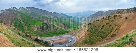 The foggy evening in Qurama Mountains the twisted highway leads from the Kamchik Pass to Tashkent Region Uzbekistan.