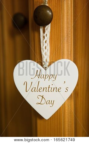 white heart hanging on door knob with the words Happy Valentines Day