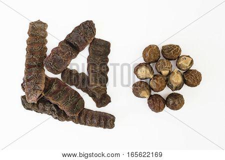Dried Shikakai pods or soap bobs (Acacia Concinna) and Soapnuts {Sapindus emarginatus} on white