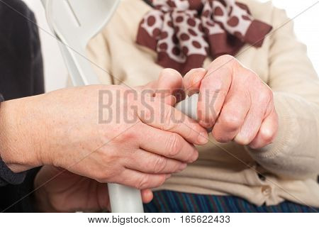 Close up picture of old female hands holding a crutch