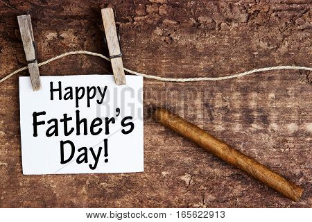 white sign hanging on clothesline with the words Happy Fathers Day and a cigar