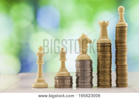 Growing coins stacks with green and blue sparkling bokeh background. Chess figures standing on coins meaning power and career growth. Financial growth saving money business finance wealth and success concept.