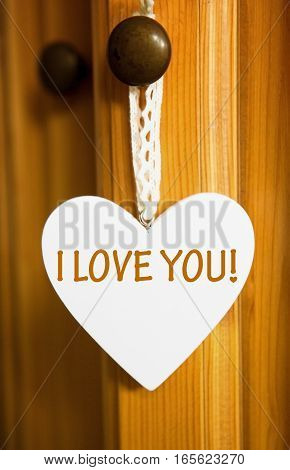 white wooden heart hanging on door knob with the words I Love You