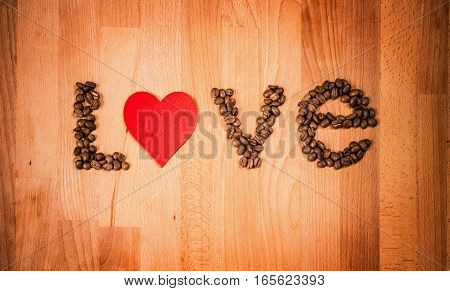Coffee beans on wood background. Shape of word Love made from coffee beans, decorated with red heart on wooden surface. Roasted coffee beans on rustic wood background. Top view.
