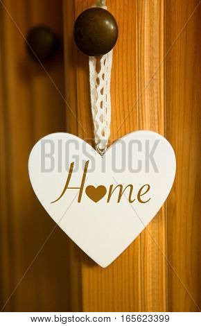 white wooden heart hanging on door with the word Home
