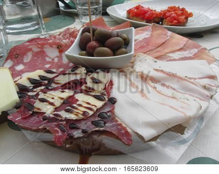 Platter of cold cuts with rustic ham prosciutto salami lard cheese and olives . Tuscany Italy