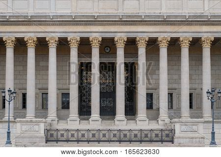 Building front of a courthouse in Lyon, France, with a colonnade of corinthian columns. This law court is held in the greek / roman looking neoclassical architectural style often used for government buildings. poster