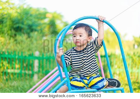 Sad Little Asian Kid Sitting On Slide At The Playground At The Day Time