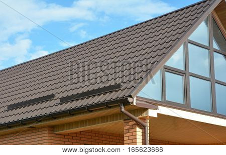 Building Modern House Construction with metal roof rain gutter system and roof protection from snow board snow bar (Snow guard). Roof Snow Guards: Building Materials & Supplies