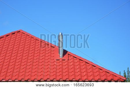 New red tiled roof with metal chimney house roofing construction exterior. Roofing Construction.