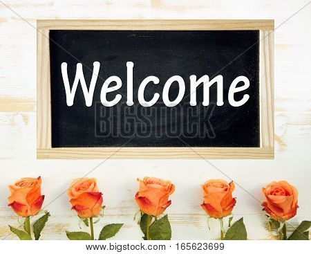 orange roses on white wooden table and chalkboard with the word Welcome
