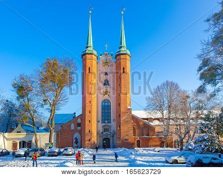 GDANSK OLIWA POLAND - JANUARY 16 2017: People on catheral square covered snow at sunny winter day.