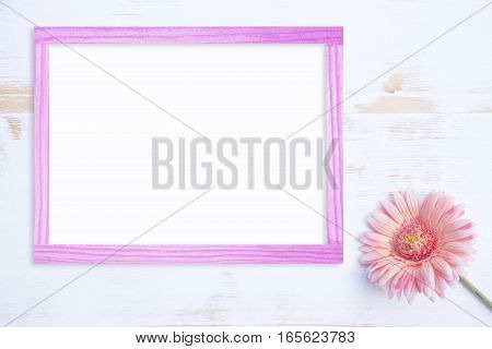 one beautiful pink gerbera on a white vintage wooden background and pink frame