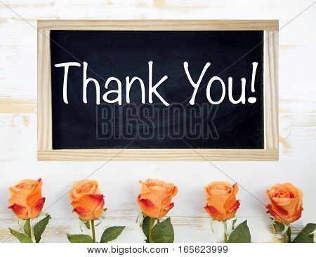 orange roses on white wooden background and black chalkboard with the words Thank You