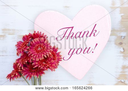 red flowers on wooden white table with heart and words Thank You