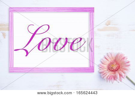 pink flower on white wooden table with frame and the word Love