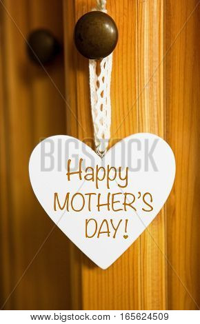 white wooden heart hanging on door with the words Happy Mothers Day