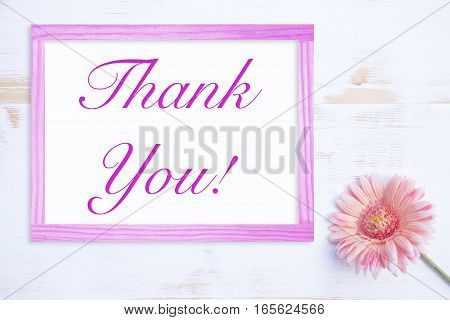 pink flower on white wooden table with farme and words Thank You
