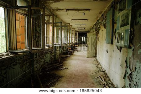 Abadoned School Corridor With Open Windows At Chernobyl City Zone Of Radioactivity Ghost Town.