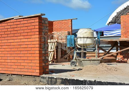 Cement Concrete Mixer on the House Construction Site. Concrete mixer Concrete blender is a device that homogeneously combines cement aggregate such as sand or gravel and water to form concrete.