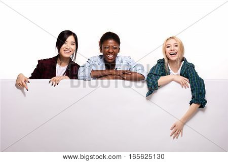 Three Different Ethnic Girls Leaning On White Panel