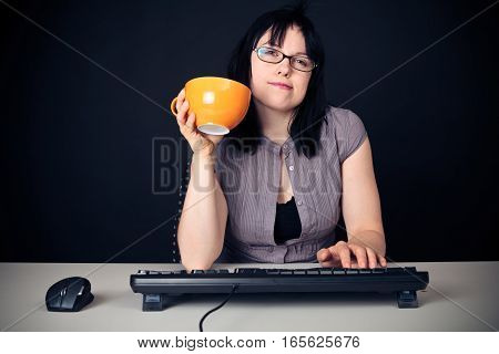 young woman with glasses sitting in front of a computer, programming.