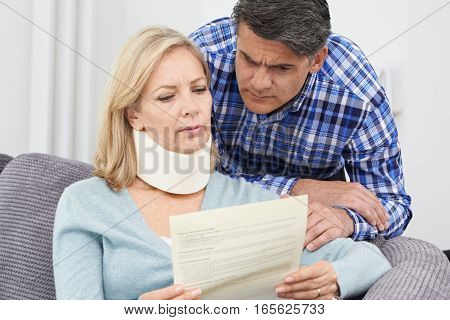 Couple Reading Letter About Woman's Neck Injury