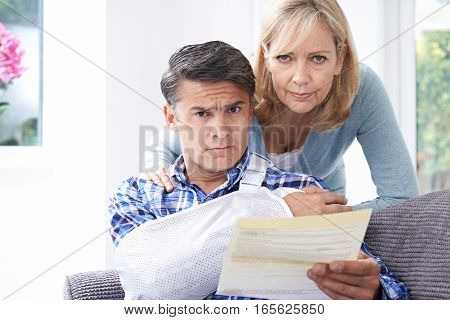 Couple Reading Letter About Man's Arm Injury