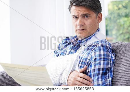 Portrait Of Mature Man Reading Letter About Injury