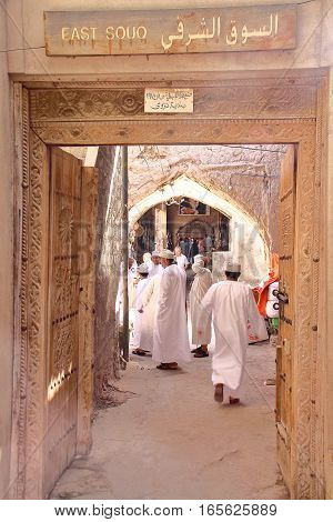 NIZWA, OMAN - FEBRUARY 3, 2012: Entrance of the East Souq in Nizwa Old Town with Omani men traditionally dressed