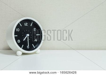 Closeup black and white alarm clock for decorate show show half past seven or 7:30 a.m. on white wood desk and cream wallpaper textured background with copy space