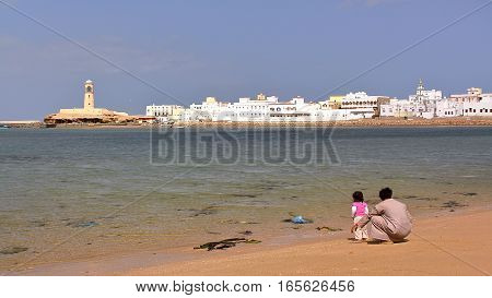 SUR, OMAN - FEBRUARY 6, 2012: View of Ayjah from the beach with an Omani man and his little daughter in the foreground