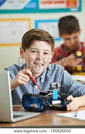 Two Male Pupils In Science Lesson Studying Robotics