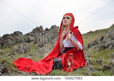 Beautiful Blonde Woman With Red Cloak Sitting On A Rock On The Edge Of A Mountain In The Sunset Ligh