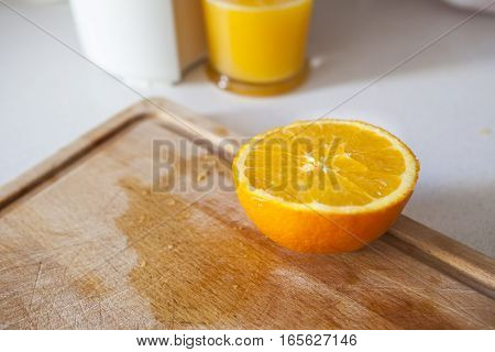 Making orange juice with juicer at kitchen with cutting board