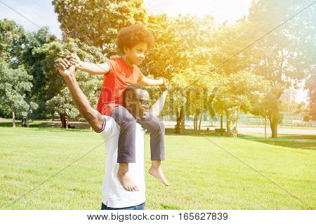 African American Family Doing Piggyback And Having Fun In The Outdoor Park During Summer