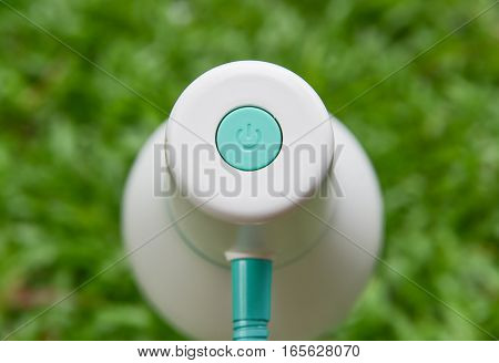 On-Off button of lamp with green grass background