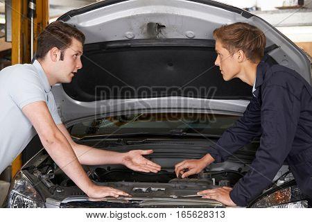 Mechanic Helping Apprentice To Fix Car Engine
